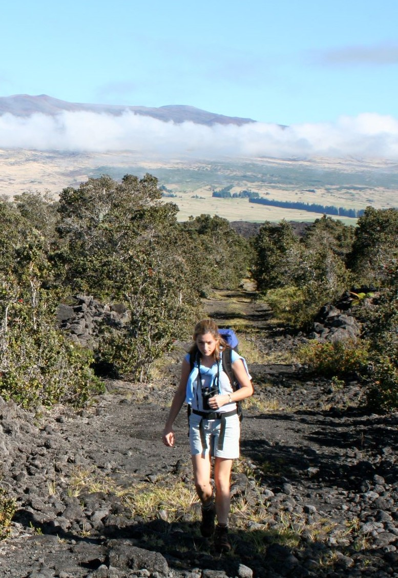Image of Marie Edmonds walking up a scree covered incline, with the profile of Mauna Kea volcano in the background