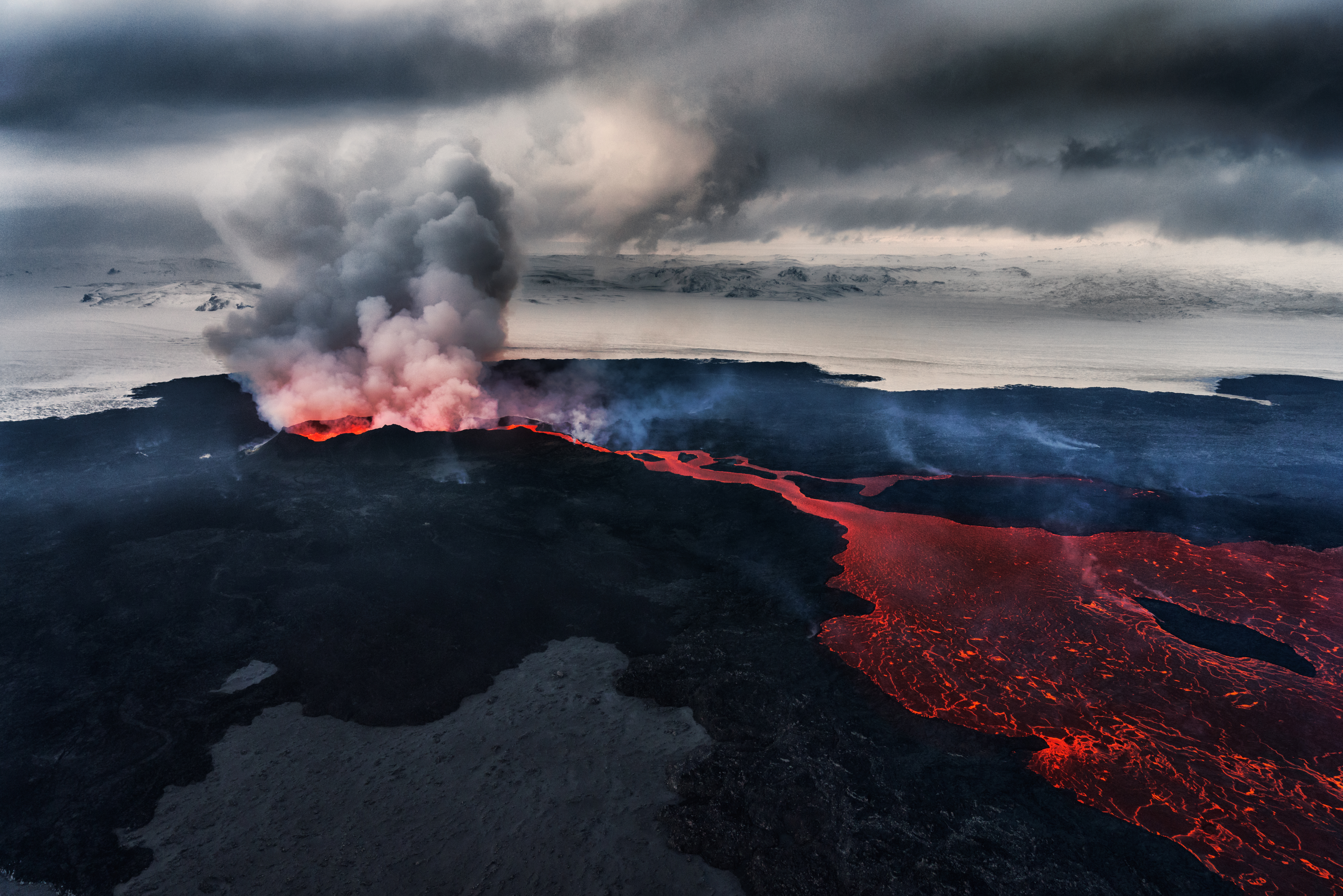 An aerial photo of the Holahraun fissure eruption, with a volcanic gas plume issuing from the vent and a lava flow extending from a mini volcanic cone across the sandur.