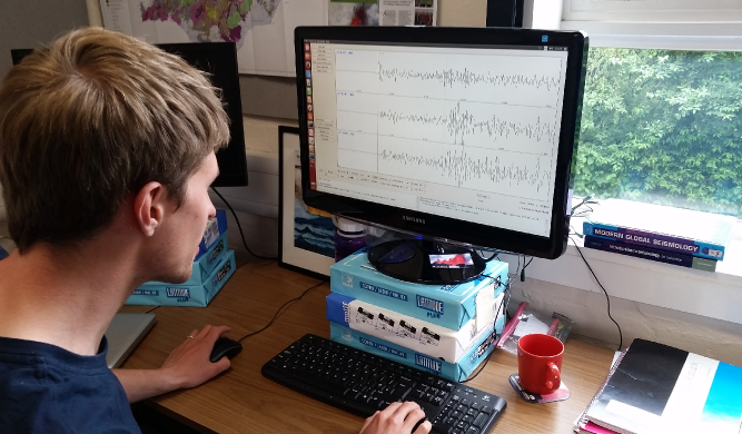 A photo of a volcanic seismologist looking at seismograms on a computer screen, selecting Icelandic earthquakes for further analysis.