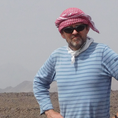 Image of Nicky standing with arms on hips at his field site in the desert