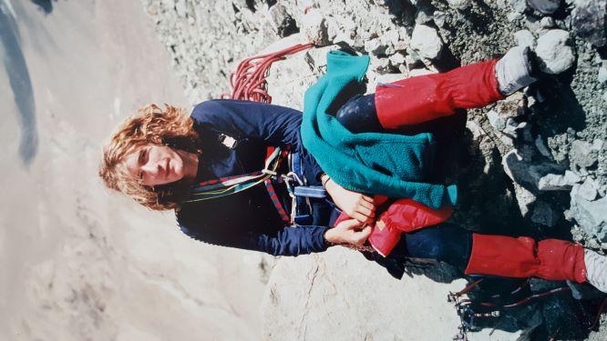 Photo of John Smallwood sat down on rocks on field work, carrying climbing gear