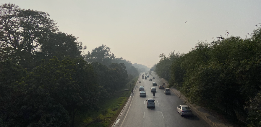 Image of a busy road in Lahore, surrounded on either side by trees and with a smoggy sky blocking out the sun