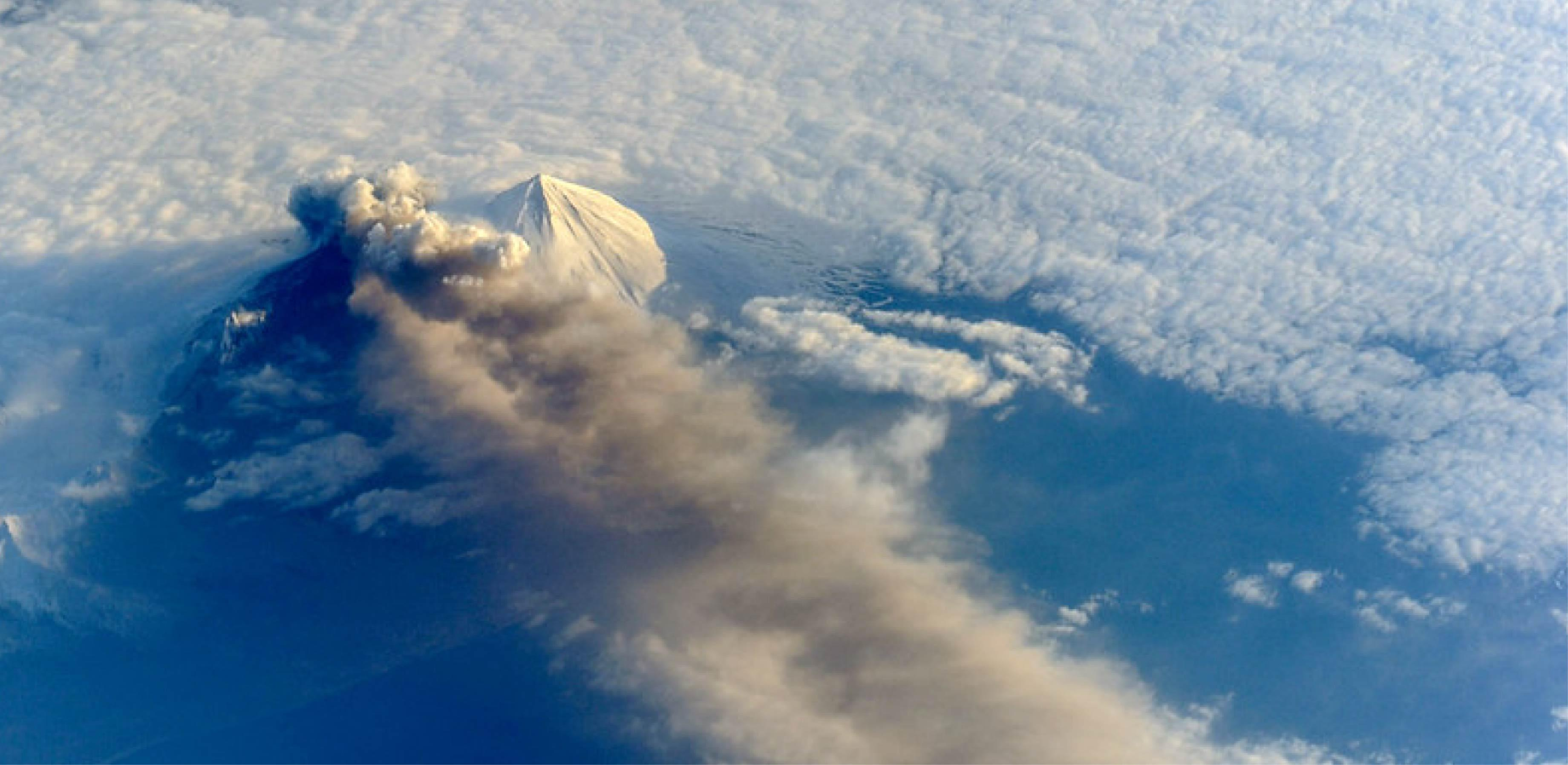 Satellite image of a volcano from space, shrouded in clouds and spewing volcanic ash