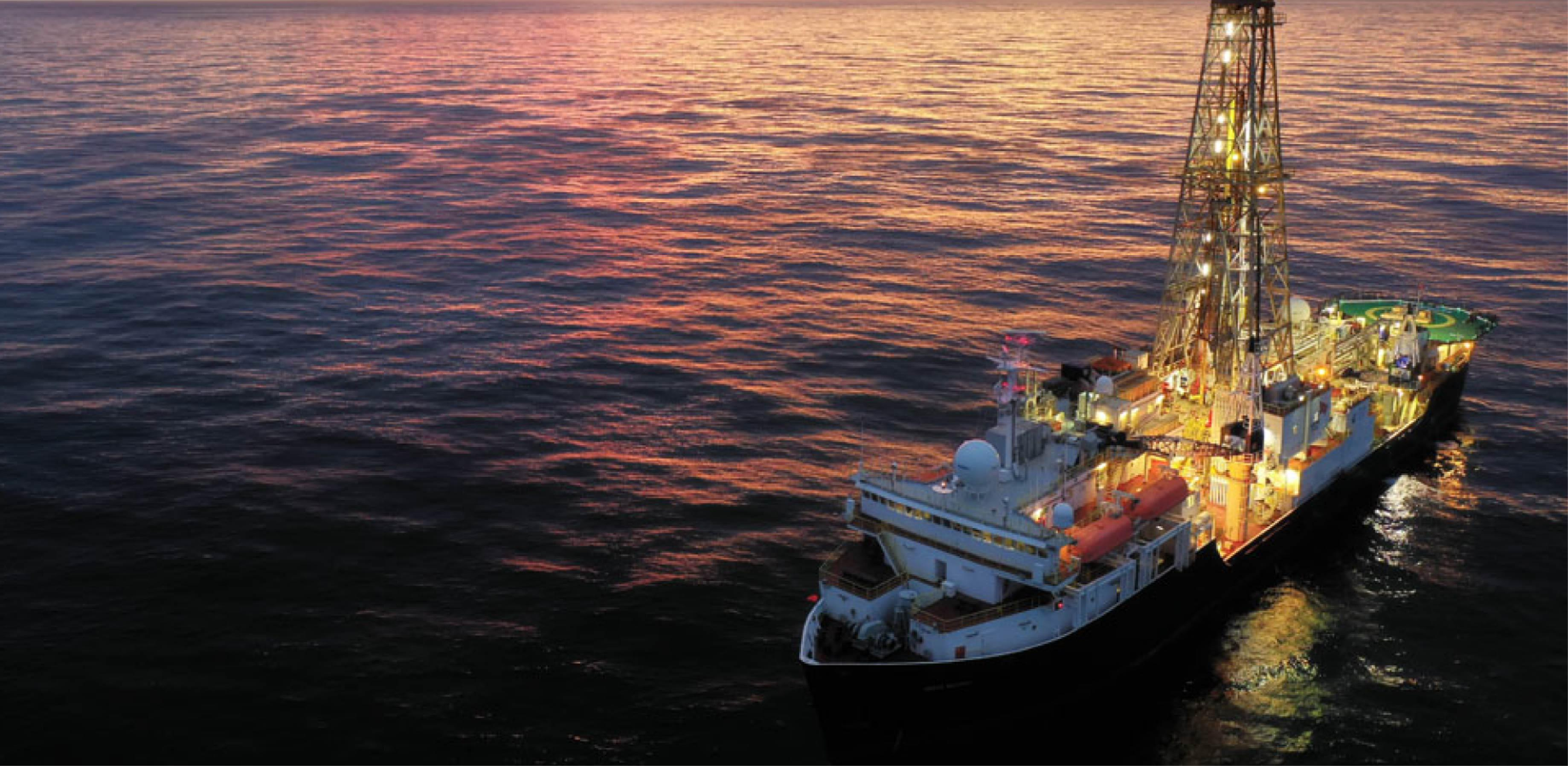 Image of sun setting behind drilling equipment on a ship