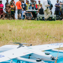 Drone ready to launch in the foreground with research scientists and Manam islanders gathered in the background; image credit Mathew Wordell