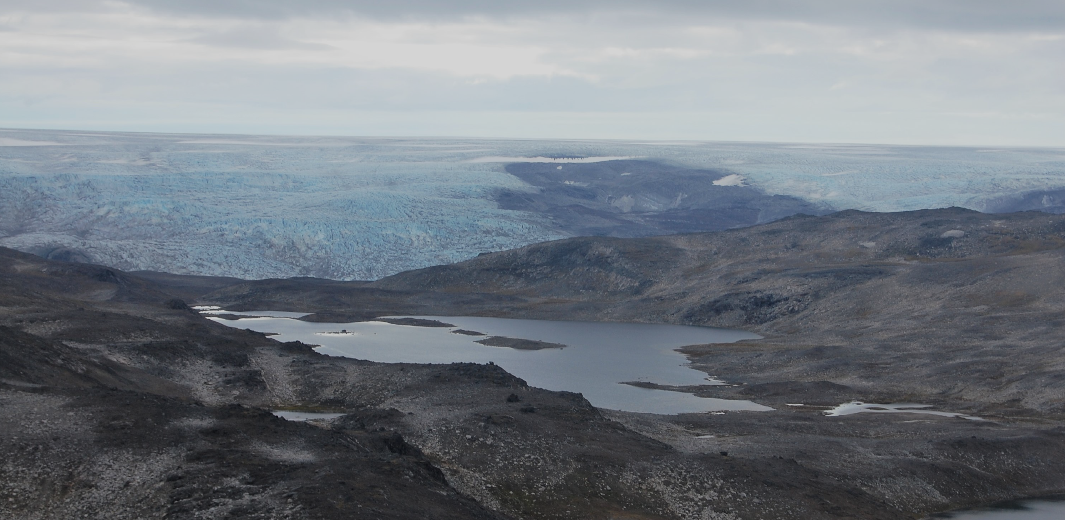 Image of Greenland landscape, with barren dark rocks in the foreground, against a backdrop of ice
