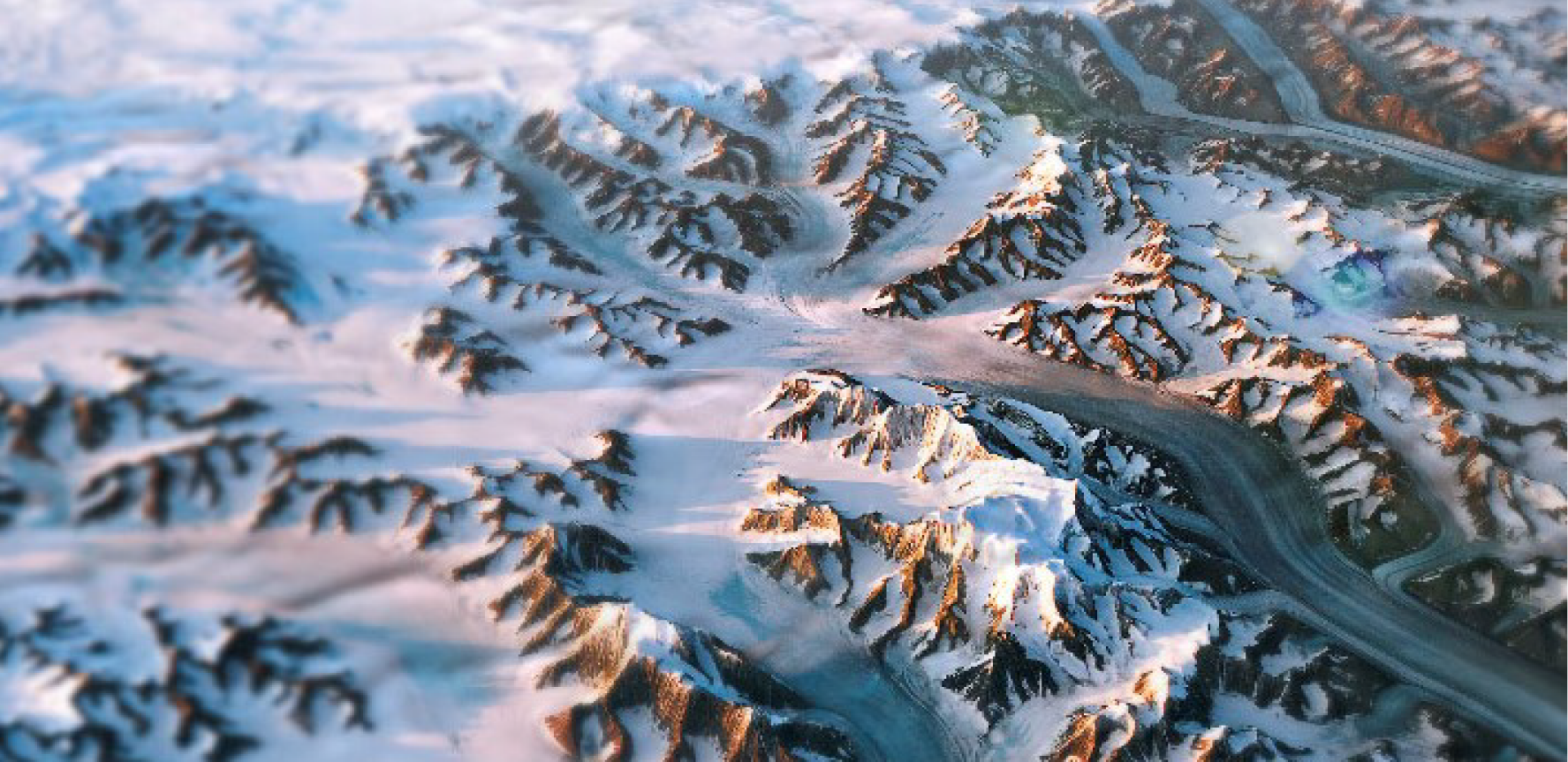 Birds eye image of Greenland glacier flowing through a snowing mountainous landscape