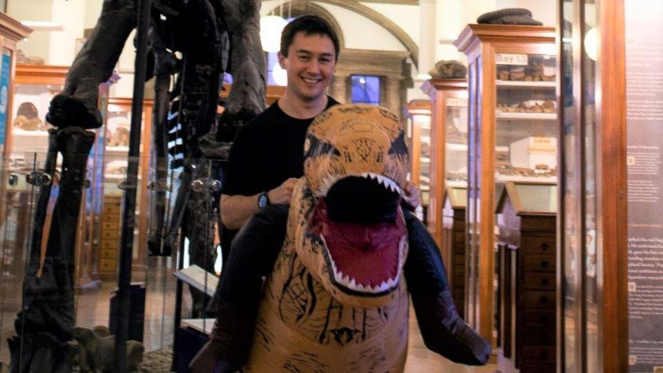 Image of a man smiling, wearing an inflatable dinosaur costume and stood inside the Sedgwick Museum