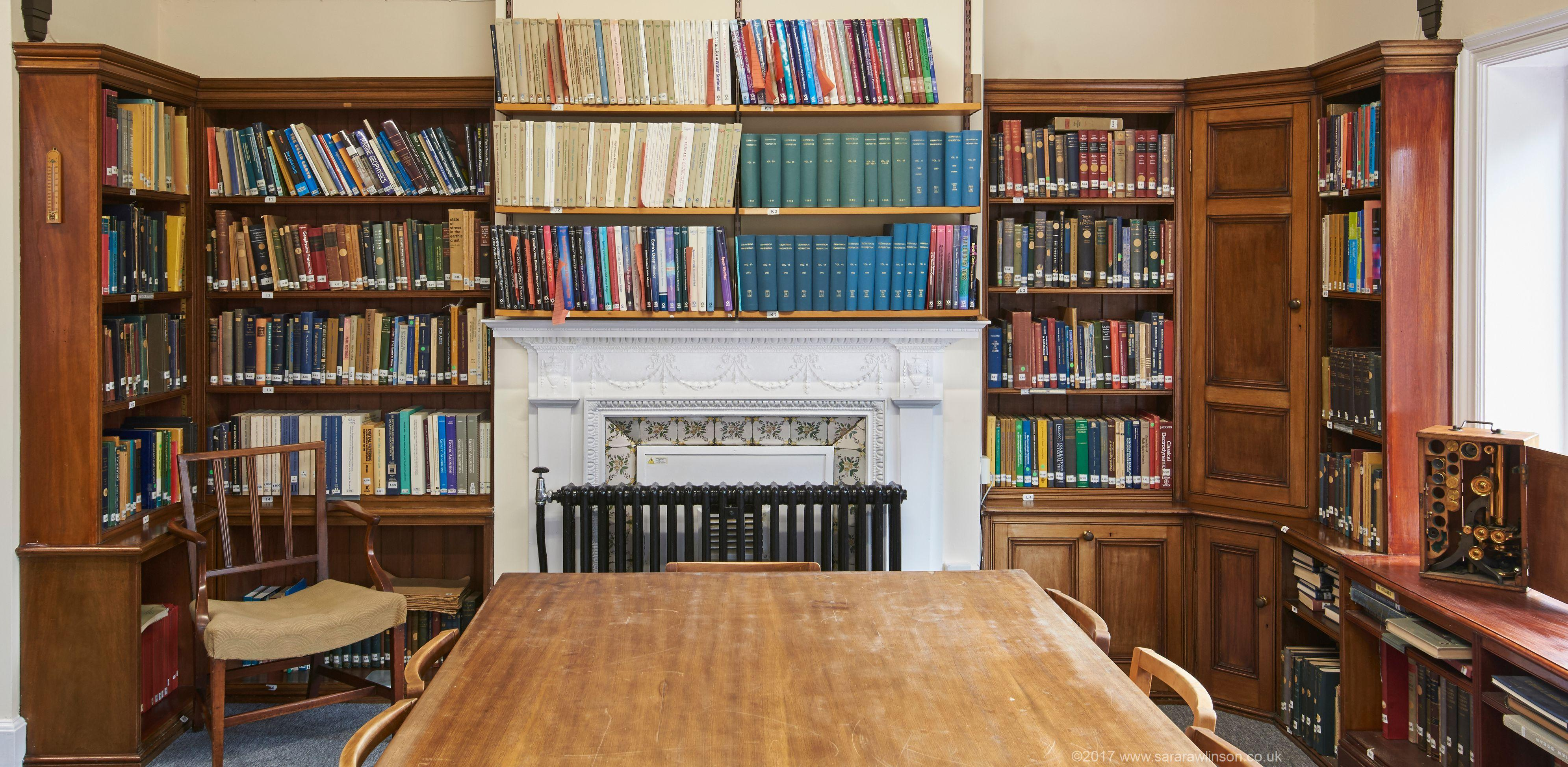 The library at the Bullard labs showing a fireplace, a table and books shelves; image credit Rawlinson copyright