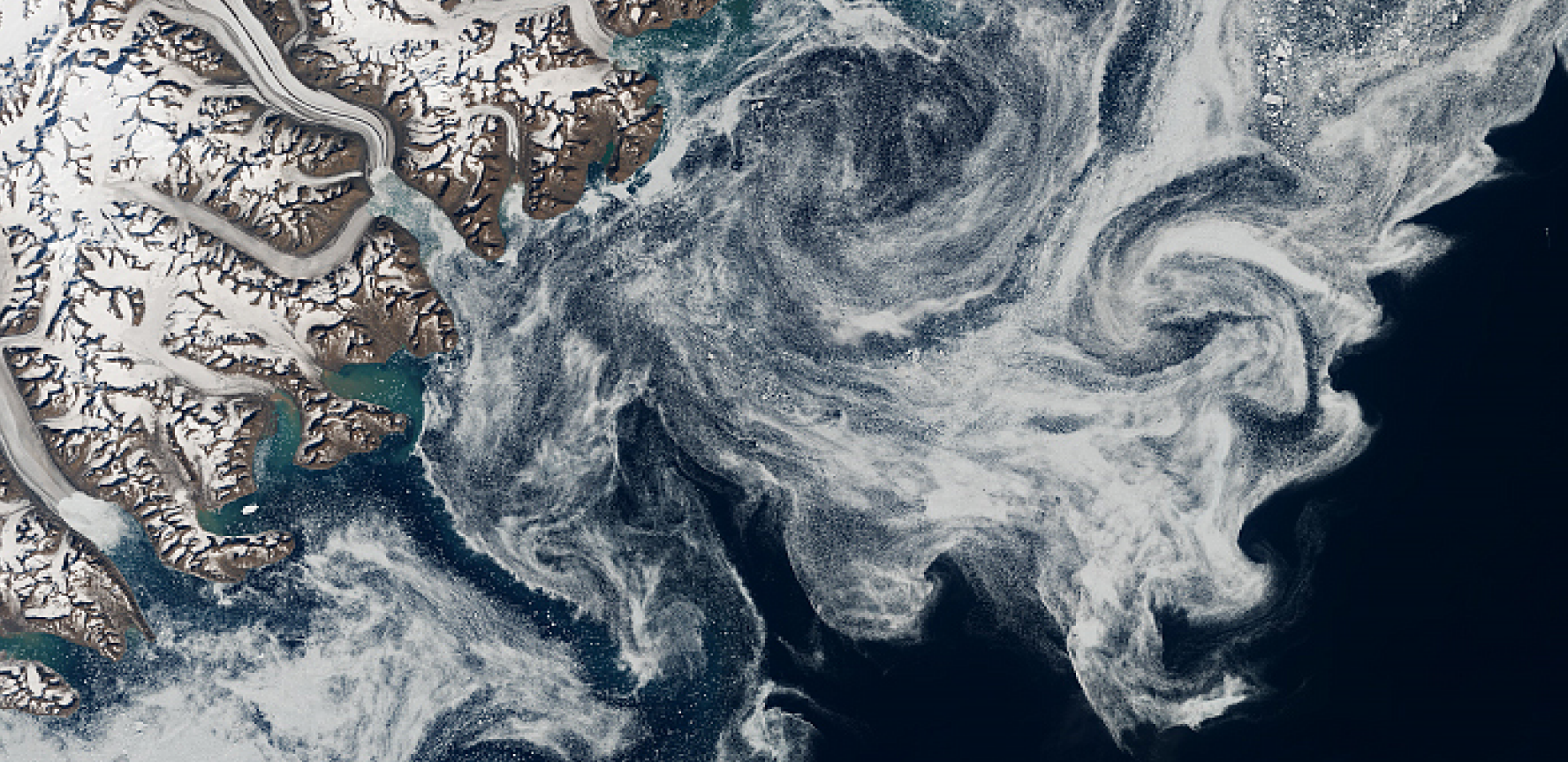 Satellite image of a frozen river meeting the sea, with sea ice floating across the Denmark Strait